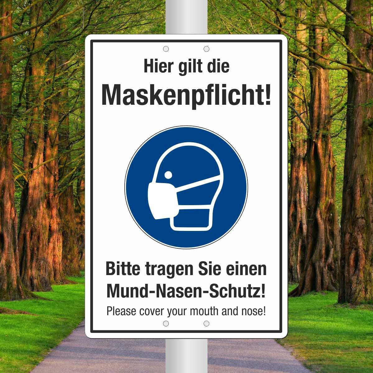 Schild 'Hier gilt die Maskenpflicht! Bitte tragen Sie einen Mund-Nasen-Schutz! Deutsch/Englisch'